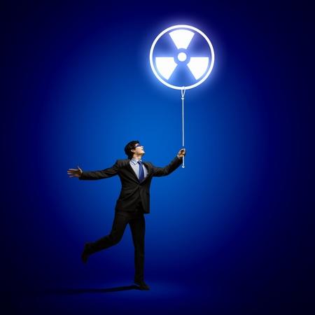 radiactividad: Imagen de hombre de negocios en gafas mirando s�mbolo de radiactividad Foto de archivo