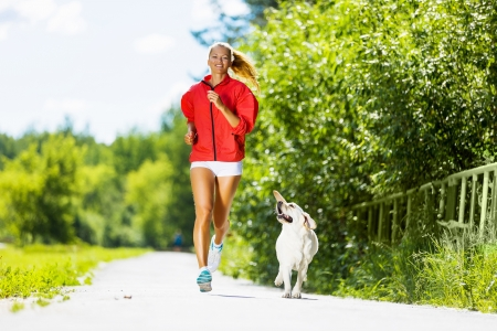 Young attractive sport girl running with dog in park photo