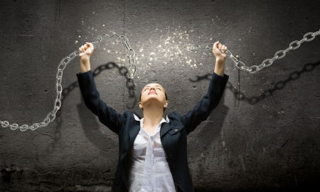 Image of businesswoman in anger breaking metal chain photo