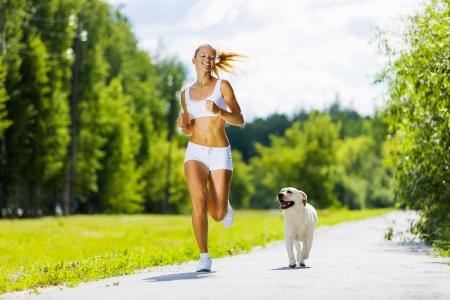 ジョグ: 公園で犬と一緒に走っている若い魅力的なスポーツ少女