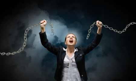 will power: Image of businesswoman in anger breaking metal chain