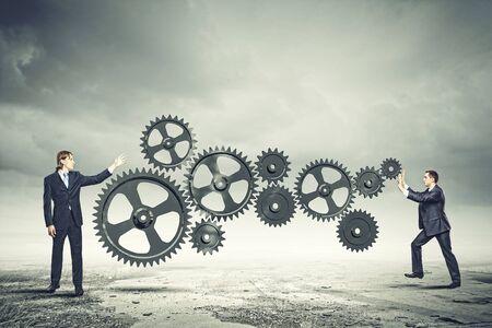 Businessman with cog wheel elements  Construction concept photo