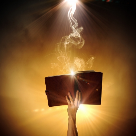 old writing: Human hand holding magic book with magic lights