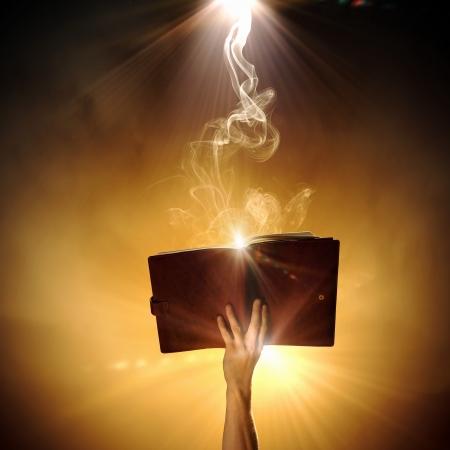 lectura y escritura: Mano que sostiene el libro de magia humana con luces m�gicas Foto de archivo