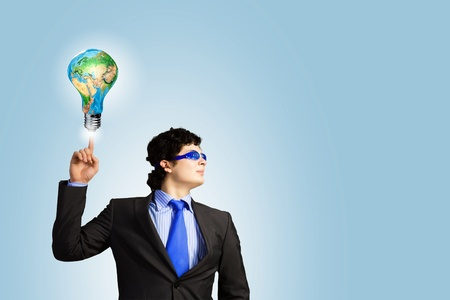 Image of young businessman with light bulb  New idea and inspiration   photo