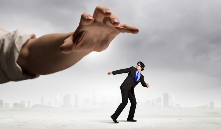funny image of businessman trying to run away from hand Stock Photo - 22138260