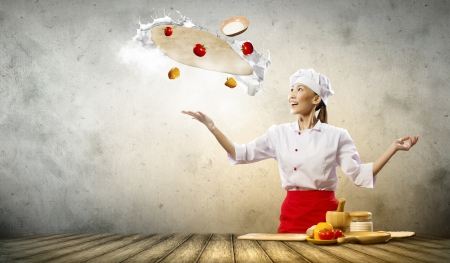 dough: Asian female cook making pizza standing against color background Stock Photo