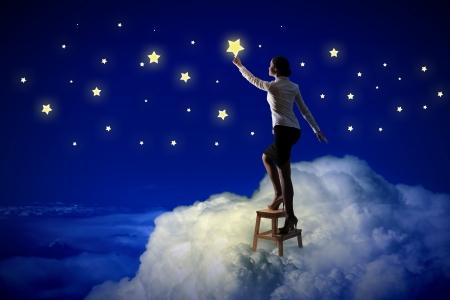 夜空の照明つ星の評価の若い女性の画像