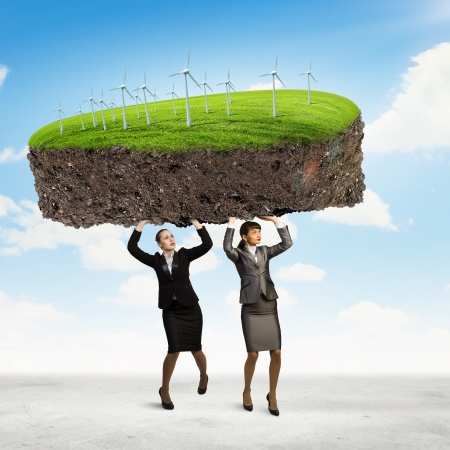 Image of two businesswomen holding lawn above head  Partnership and ecology photo