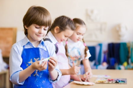 Little children painting and playing at kindergarten Stock Photo