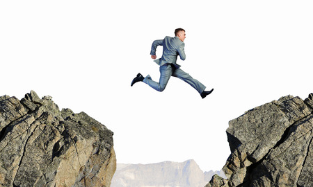 Image of young businessman jumping over gap 版權商用圖片