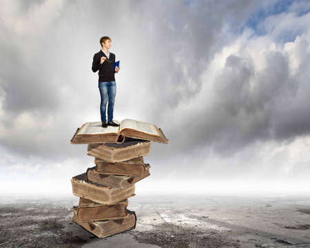 Image of little cute boy standing on pile of books photo