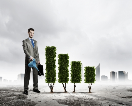 Image of businessman watering plant shaped like graph photo