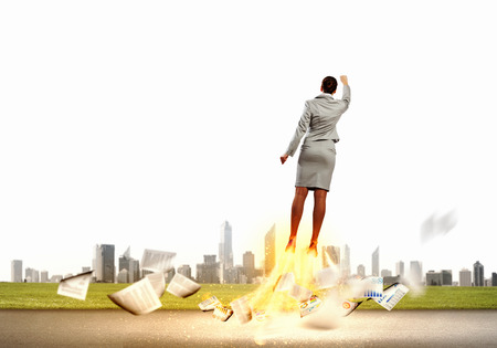 Image of businesswoman flying up into sky Stock Photo