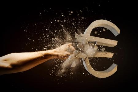 dinero euros: Cierre de la imagen de la mano del hombre rompiendo la piedra símbolo del euro