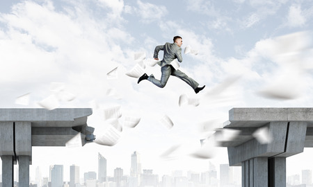 Image of young businessman jumping over gap in bridge Stock Photo - 23346907