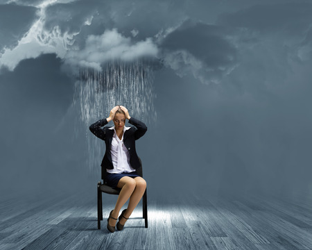 joblessness: Image of young troubled businesswoman standing under rain