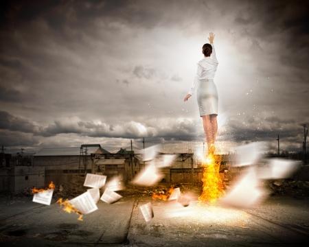 v�locit�: Image de la femme d'affaires volant haut dans le ciel