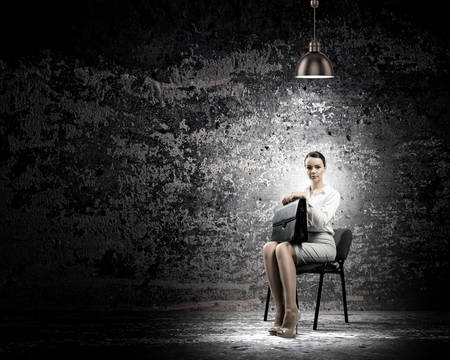 Image of young businesswoman sitting on chair under spot of light photo