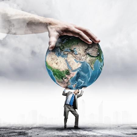 Afbeelding van een jonge ondernemer onder druk van de planeet Aarde Elementen van dit beeld zijn geleverd door NASA Stockfoto