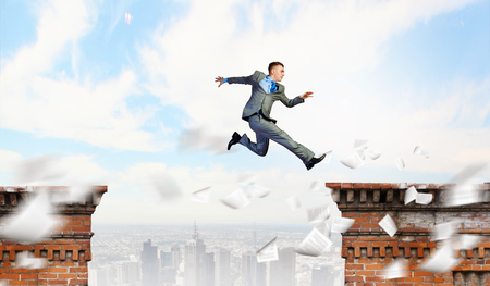 Image of young businessman jumping over gap in bridge Stock Photo - 23404256