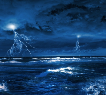 Image of dark night with lightning above stormy sea photo