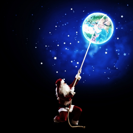 Image of Santa Claus in red costume with Earth planet photo