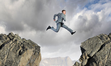 risking: Young businessman jumping over mountain gap  Risking in business