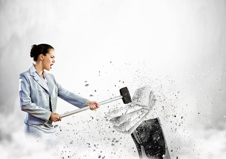 Image of businesswoman crushing with hammer pile of keyboards photo