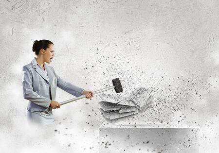 Bild der Unternehmerin Zerkleinern mit Hammer Haufen von Tastaturen