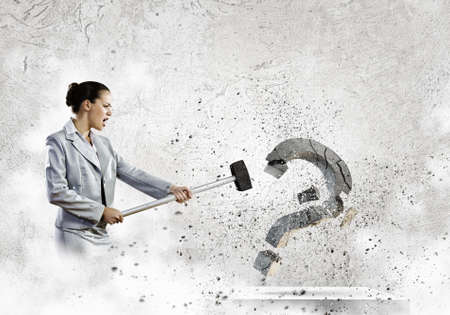 Image of businesswoman destroying with arm stone question mark photo