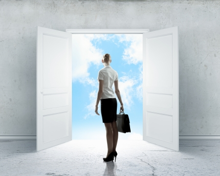 Image of businesswoman standing in front of opened door photo