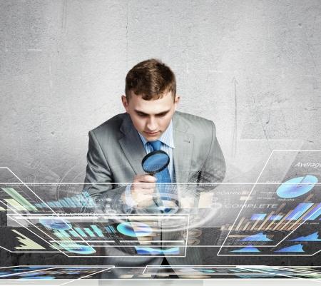 zvětšovací sklo: Obrázek podnikatel zkoumání objektů s lupou Reklamní fotografie
