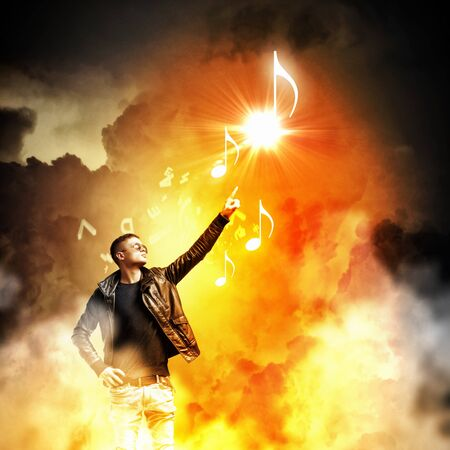rock star: Image of young man rock musician in lights Stock Photo