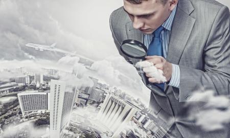 Immagine di uomo d'affari esaminando oggetti con la lente di ingrandimento