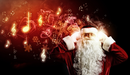 Image of Santa Claus in red costume wearing earphones photo