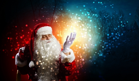 Image of Santa Claus in red costume against dark background Stock Photo