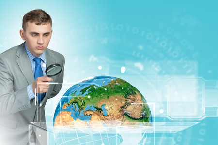 optical people person planet: Image of businessman examining objects with magnifier  Elements of this image are furnished by NASA