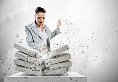 Image of businesswoman breaking bricks with hand Stock Photo