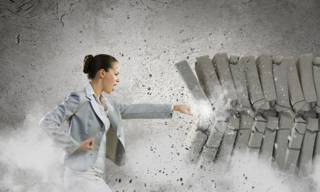 Image of businesswoman breaking bricks with hand Banco de Imagens
