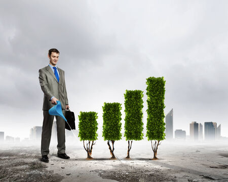 watering plants: Image of businessman watering plant shaped like graph Stock Photo