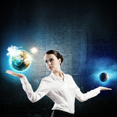 Image of businesswoman holding Earth planet and moon on palms photo