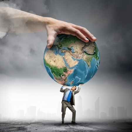 under pressure: Image of young businessman under pressure of planet Earth  Elements of this image are furnished by NASA Stock Photo