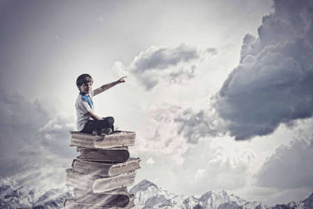 Image of little cute boy sitting on pile of books photo