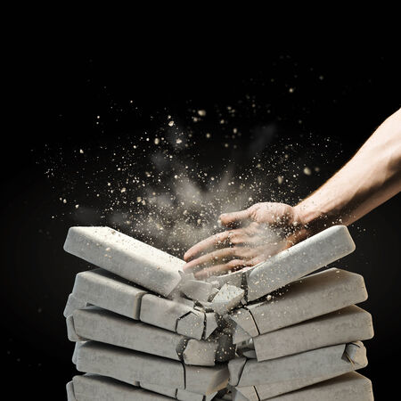 Close up of human hand breaking bricks Stock Photo