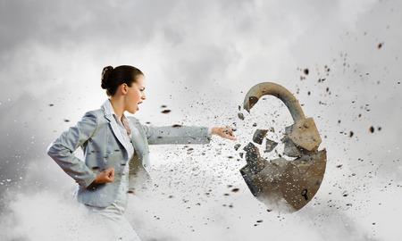 Image of businesswoman crashing lock with hand photo