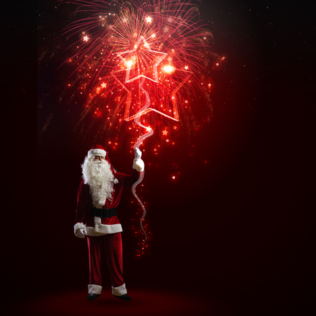 Image of Santa Claus in red costume with christmas tree photo