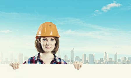 Image of young woman builder wearing helmet and holding blank banner photo