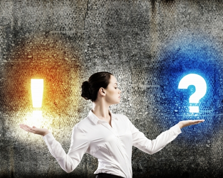 Image of businesswoman holding exclamation and question marks on palms