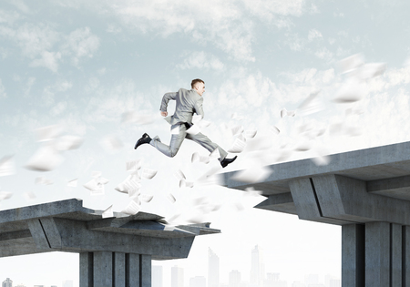 Image of young businessman jumping over gap in bridge Stock Photo - 23500287